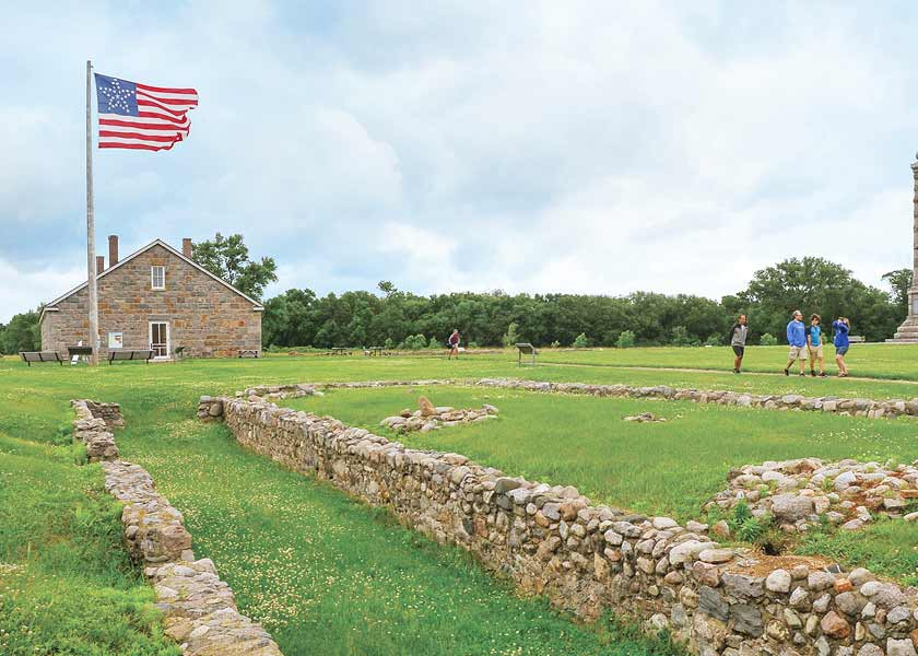 American flag on pole in front of stone fort.