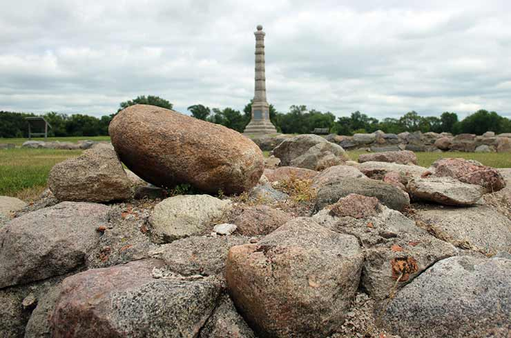 A monument with a pile of rocks in the foreground.