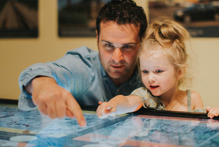 Man and little girl point at interactive map.