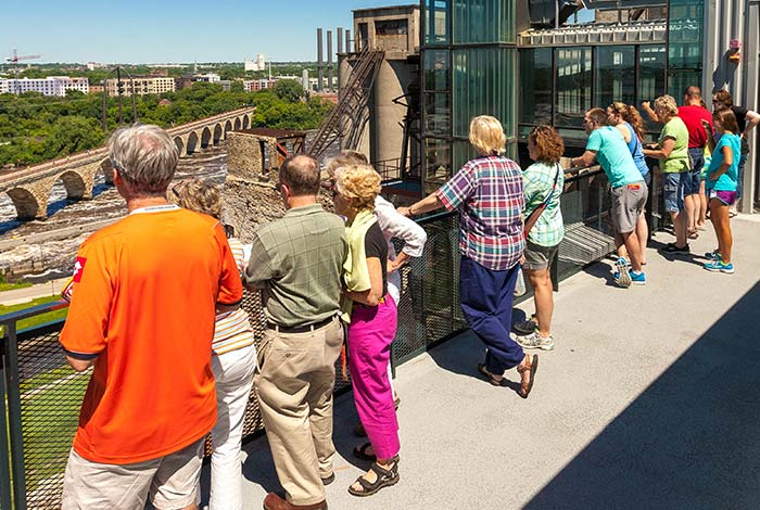 People standing on the observation deck looking at the river and cityscape.