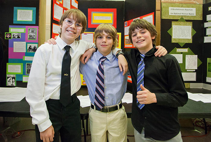 Three boys standing in front of poster board.