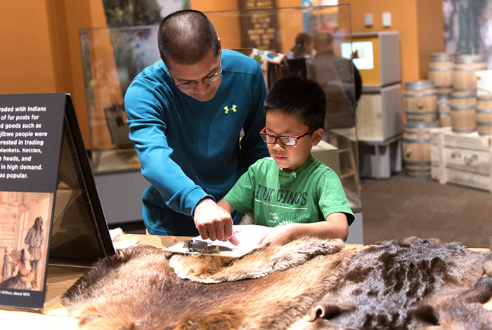 Man and little boy take notes in an exhibit.
