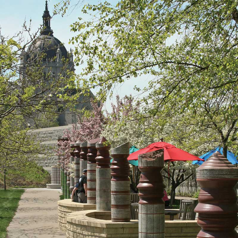 Rounded beams stand in a line with the St. Paul Cathedral in the background. Brooks Family Courtyard.