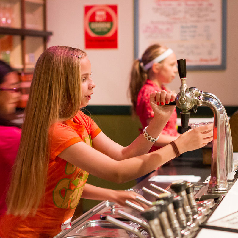 A girl pretending to pour soda from a 1930's era soda fountain.