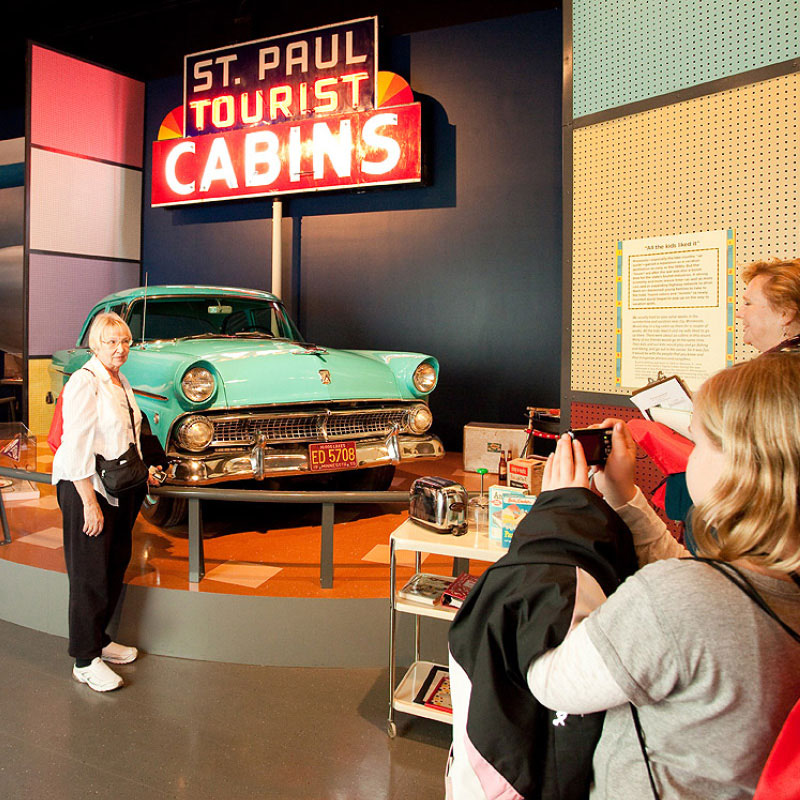 A woman standing in front of a 50's era car and a sign that says Saint Paul tourist cabins.
