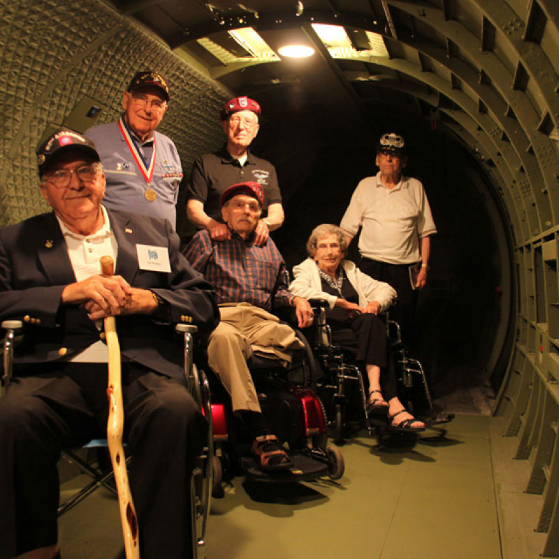 A group of military veterans standing and sitting inside the hull of an aircraft.