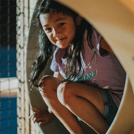 A girl crouches at the entrance of a tunnel in a play park.