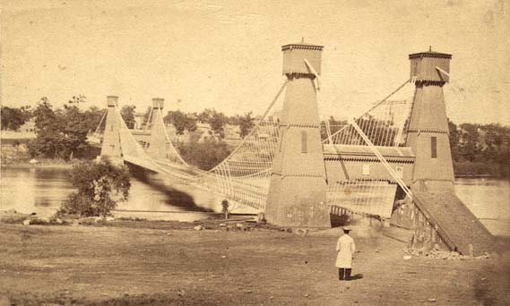 A man standing in front of a cable bridge that is spanning the Mississippi river.