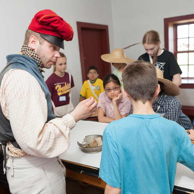 A costumed teacher portraying an engineer at Fort Snelling speaking with enthusiasm to a group of kids.