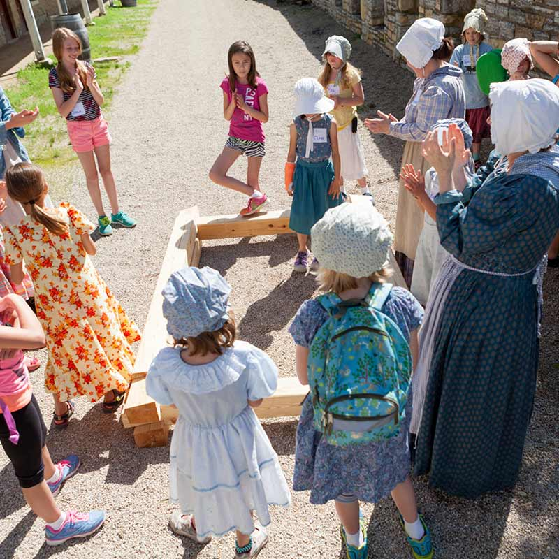 A group of young girls in bonnets gather around a costumed camp guide on a gravel path.