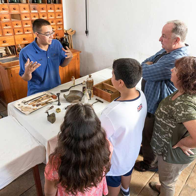 A family listens as a Fort Snelling staff person talks about historic objects displayed on a table.