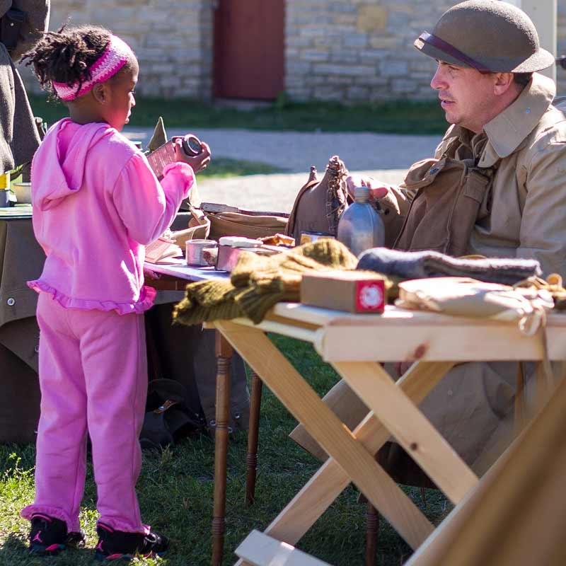 A young child approaches a costumed guide portraying a soldier stationed at Fort Snelling.