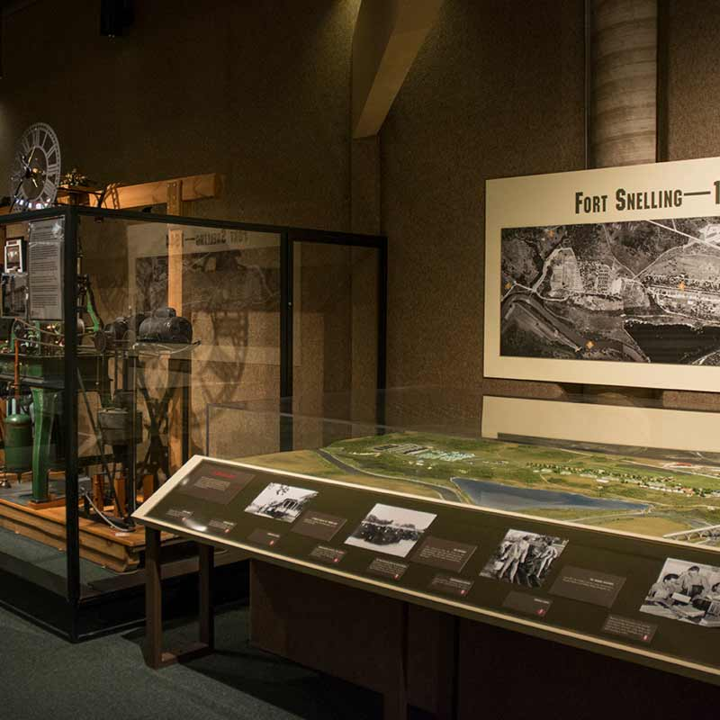 An exhibit space featuring historical objects and photos at Fort Snelling.