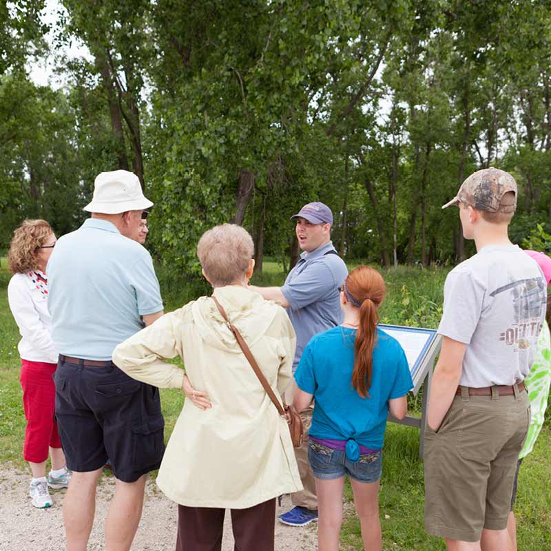 A group of visitors gathers around a tour guide on the grounds of Fort Snelling.