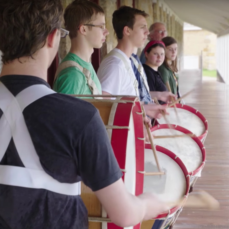Young people playing the drums at Fort Snelling.