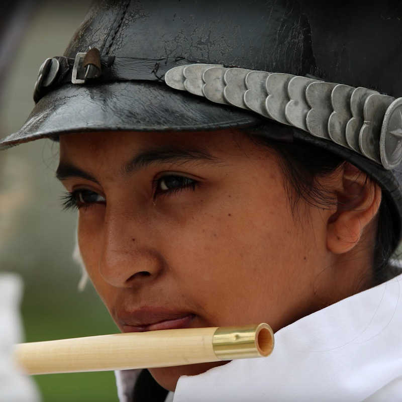 A young person playing the flute in period costume.