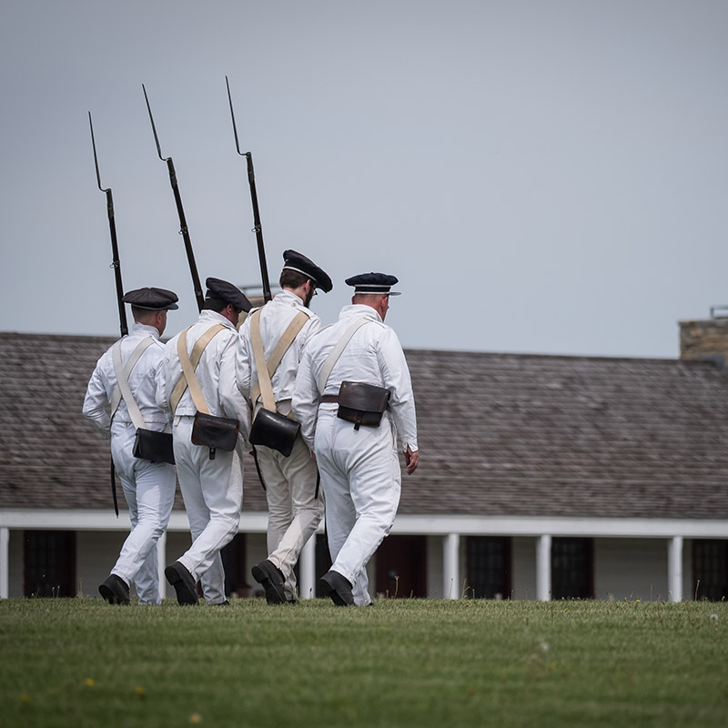 Four interpreters dressed as soldiers walk in formation.