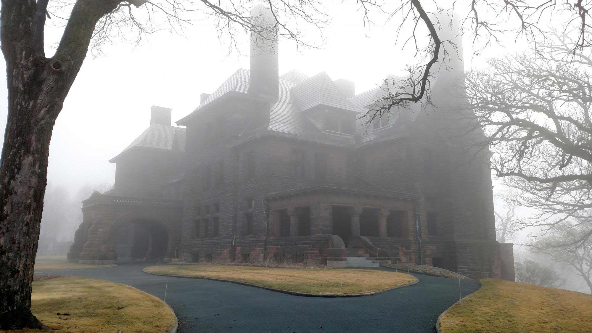 Hill House in dense fog with a leafless tree bordering the image