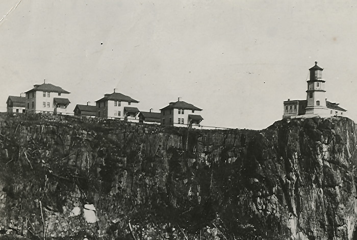 Black-and-white image of the cliff with three identical buildings on the left and the lighthouse on the right
