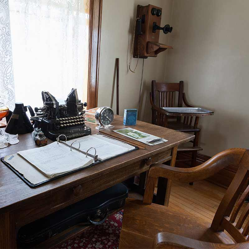 A desk with a binder and maritime equipment, wooden high chair, antique wall telephone