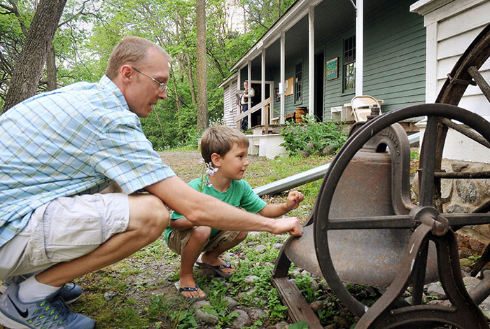 A father and son crouch down outside to look at a large antique bell.