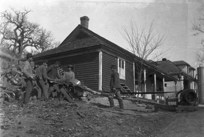 A black and white photo of workers at a log splitter.