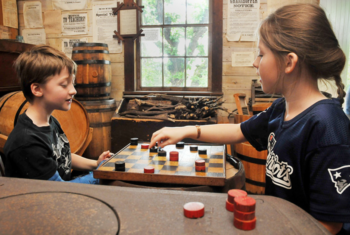 A young boy and girl sit and play checkers on a tabletop in the Harkin Store.