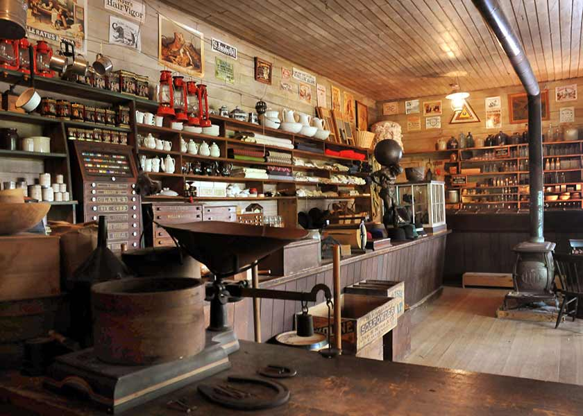 Goods such as dishes, bolts of material, bottles of medicine, and crocks sit on shelves inside the Harkin Store.
