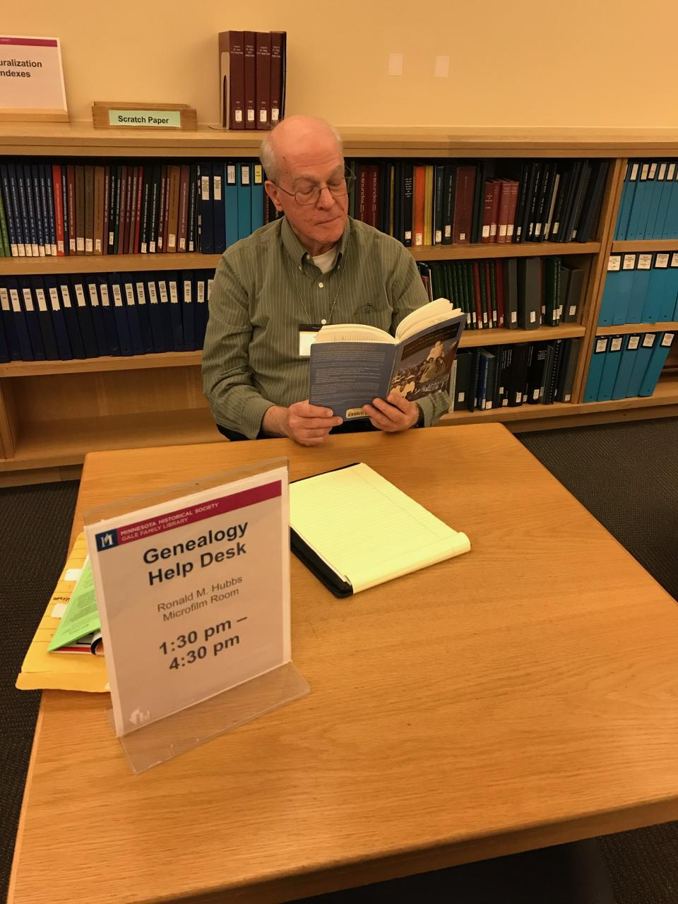 Man reading a book while sitting at a table in the library