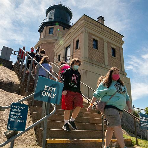 People wearing masks exit Split Rock Lighthouse.