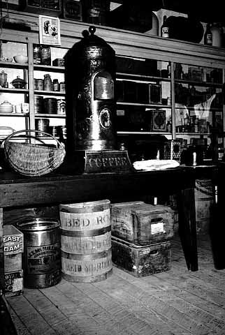 Interior of the Meighen Store, showing canned goods and coffee on the shelves and barrels on the floor. Source: MNHS Collections.