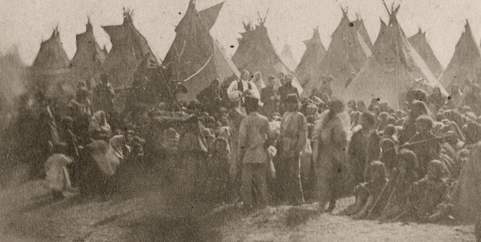 Historic photo of people gather in front of tipis.