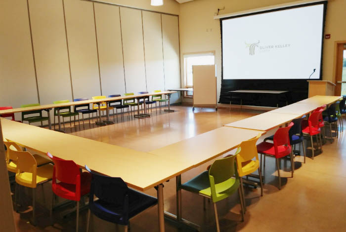 Classroom with tables arranged in a U shape, colorful chairs, and a large projector screen.