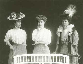 Three women, all in the same skirt and blouse, the first with a fancy hat, the second without a hat, and the third with a feathered hat and coat