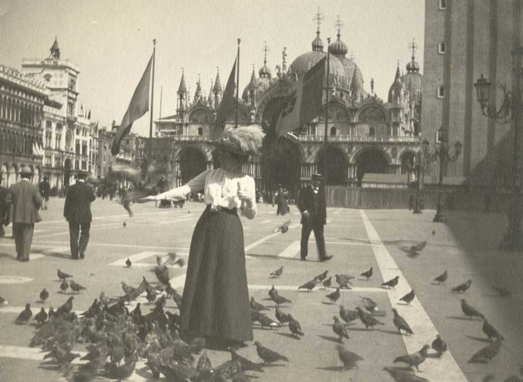 A woman surrounded by pigeons in a city square