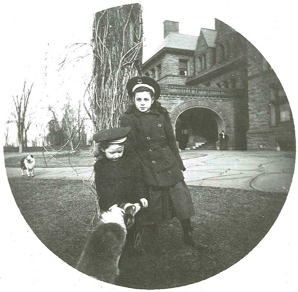 Two children and a dog in front of the James J. Hill House