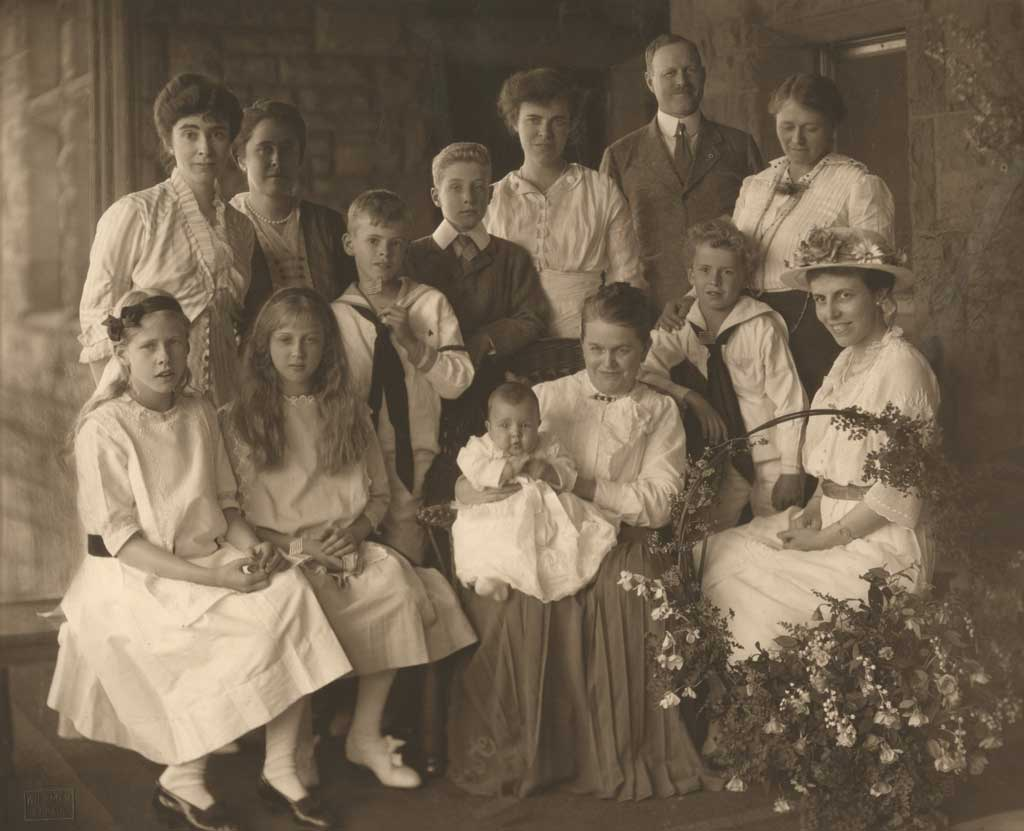 Mary Hill seated and holding a baby in the center, with 11 people on both sides and behind