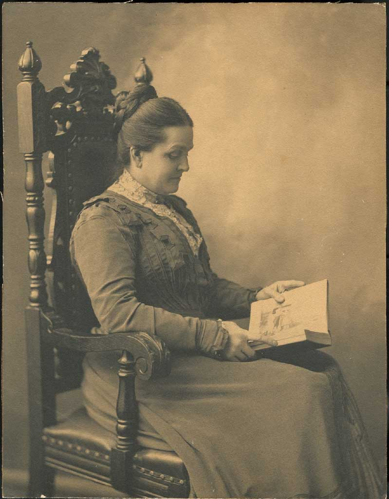 Mary T. Hill reading in a chair, facing right