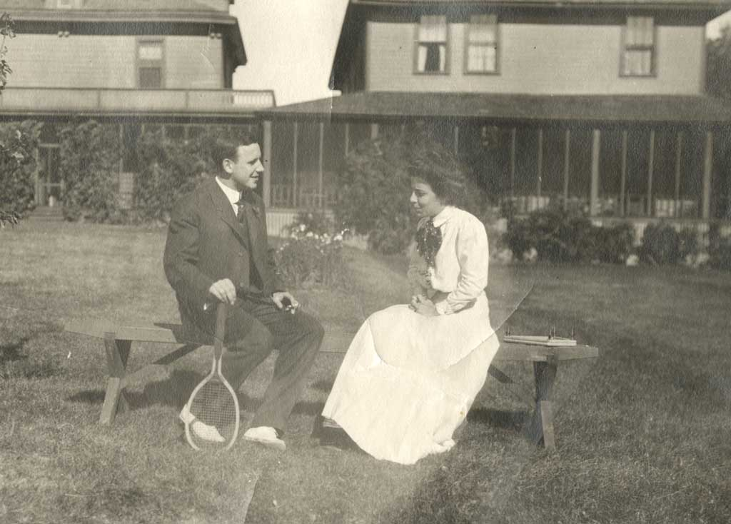 A man and a woman seated on a bench in the yard