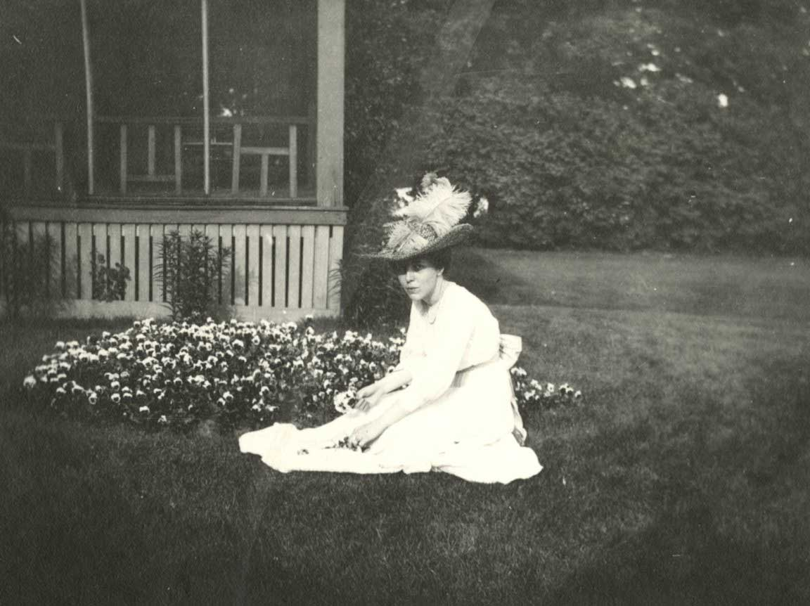 A woman sitting in the lawn next to some flowers
