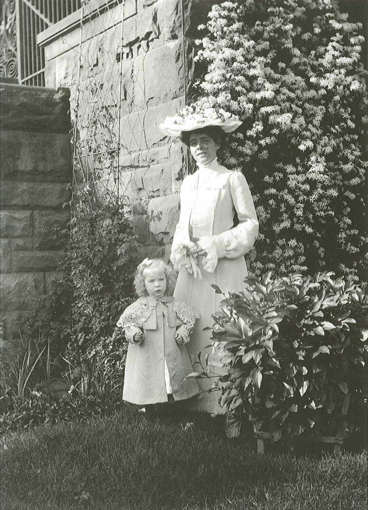 A woman in a hat standing next to a toddler in front of a flowering bush