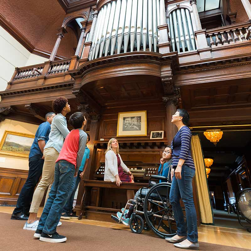 Woman sitting at large pipe organ with people looking up at the pipes.