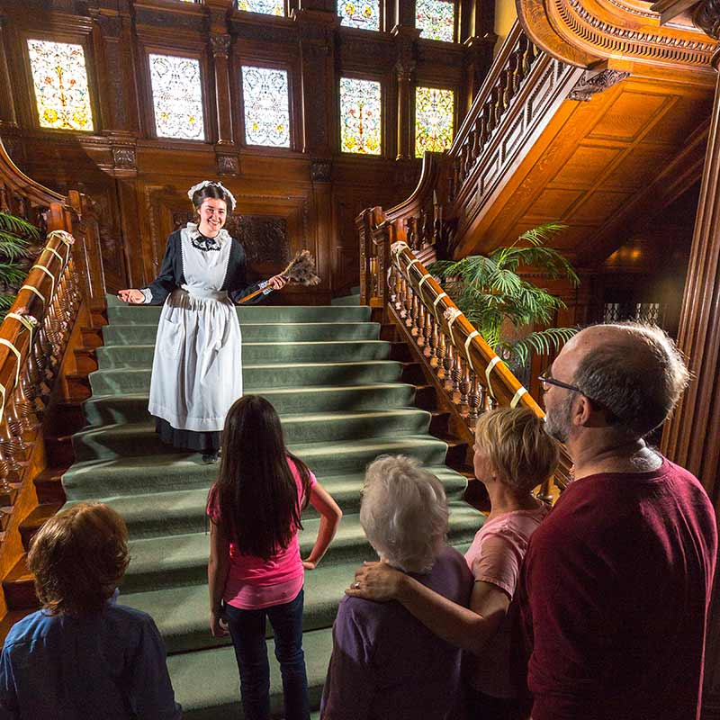 Woman dressed as maid standing on main staircase in front of tour group