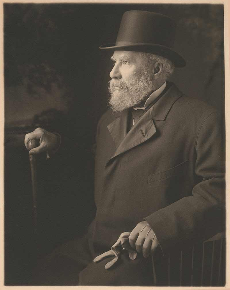 Portrait of James J. Hill wearing top hat and overcoat, facing left