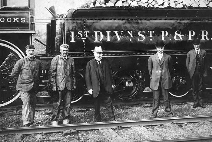 James J. Hill poses in front of a locomotive with four other men