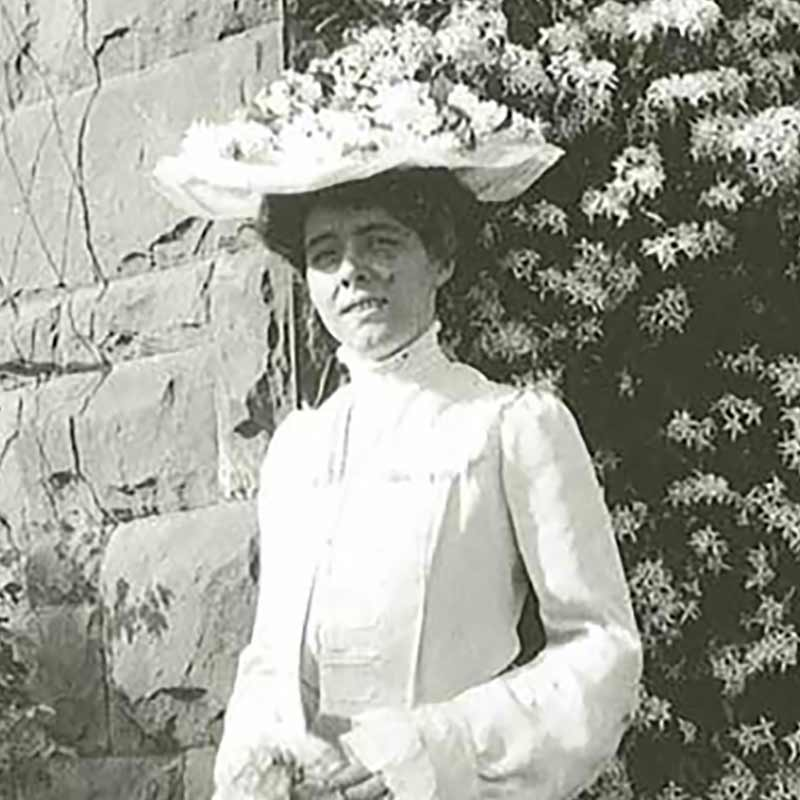 Ruth Hill posing in front of a flowering bush