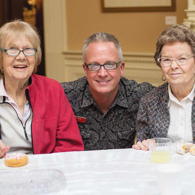 Man sitting between two women