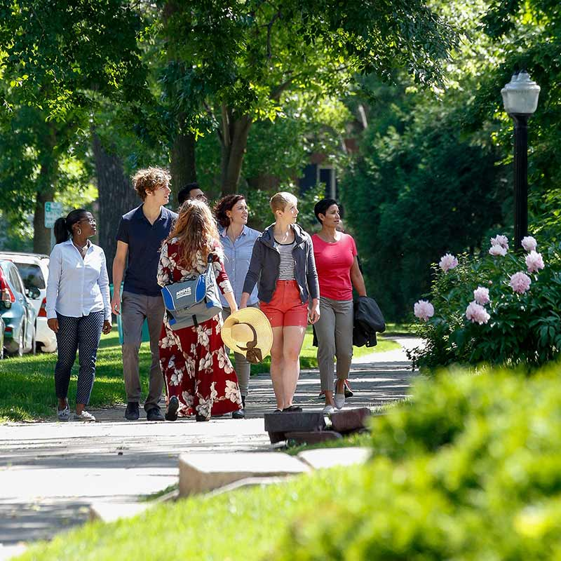Group of people walking down a sidewalk behind a tour guide and looking to the right