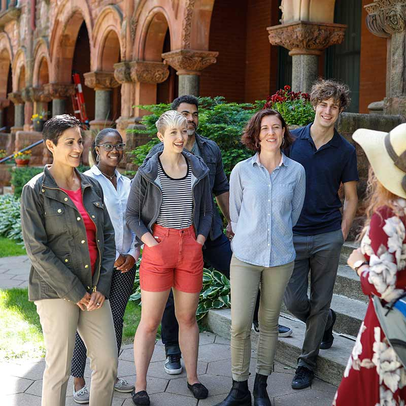 Group of people listening to tour guide while standing in front of historic home