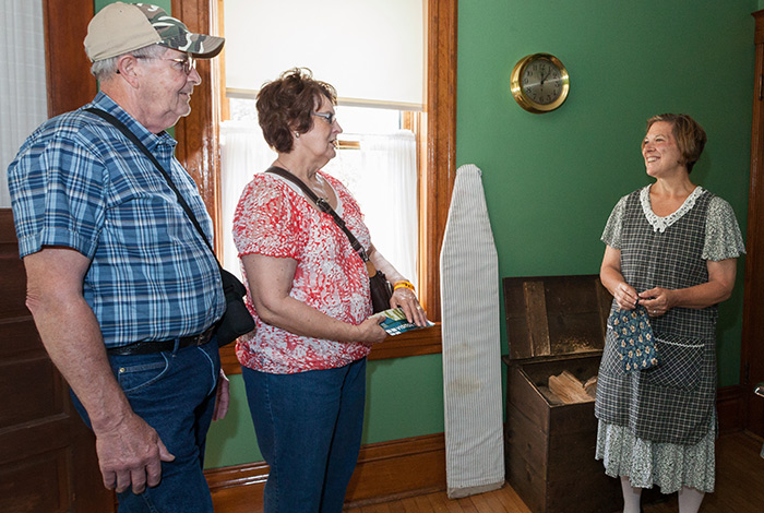 Two people talking to a costumed interpreter inside the lightkeeper's house